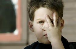 De jongen met dient voorzijde van zijn gezicht in Stock Afbeelding