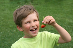 De jongen met een aardbei Stock Foto