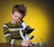 De jongen met een microscoop en kleurrijke flessen op a Royalty-vrije Stock Foto's