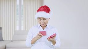 De jongen met Kerstmanhoed opent giftdoos stock videobeelden