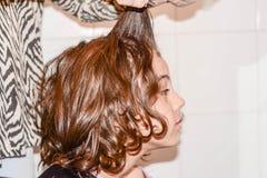 De jongen met lang haar krijgt zijn die haar door kapper wordt gesneden Stock Afbeeldingen