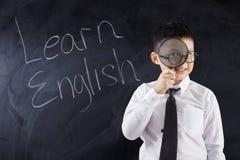 De jongen met meer magnifier en de tekst leren het Engels Royalty-vrije Stock Foto