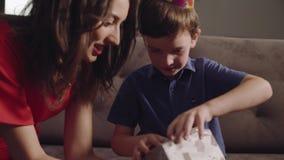 De jongen met moeder opent een verjaardagsgift stock footage