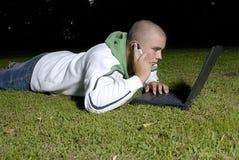 De jongen met notitieboekje en de cel telefoneren in park royalty-vrije stock afbeeldingen