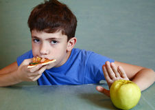 De jongen met pizza weigert om appel te eten Stock Foto's