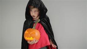 De jongen met pompoen kleedde zich als vampier voor Halloween-partij, Truc of behandelt stock videobeelden