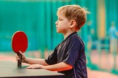De jongen met de racket voor pingpong Stock Afbeelding
