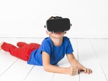 De jongen met rode broeken en blauw overhemd gebruikt thuis virtuele 3d glazen stock afbeeldingen