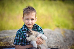 De jongen met schor puppy stock afbeelding