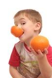 De jongen met sinaasappelen Stock Fotografie