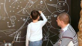 De jongen met vader schildert een beeld op de muur met krijt op een Kerstmisthema stock footage