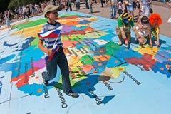 De jongen met vlag loopt op een raadsel van kaart van Rusland op de Onafhankelijkheidsdag van Rusland in Volgograd Royalty-vrije Stock Afbeelding
