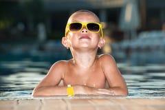 De jongen met zonnebril die in de pool rusten De vakantie van de zomer stock foto's