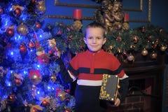 De jongen naast een gloeiende blauwe Kerstboom en een open haard Stock Foto