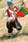 De jongen in nationaal kostuum met de Bulgaarse vlag bij het Festival van Rozhen 2015 Stock Foto's