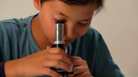 De jongen neemt de lens van de microscoop op stock video