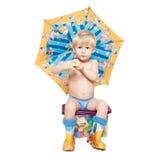 De jongen onder een paraplu zit op een doos Stock Fotografie