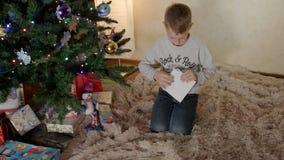 De jongen onder nieuwe jaarboom zet een brief aan Kerstman in een envelop stock videobeelden