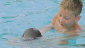 De jongen onderwijst de baby om in de pool te duiken stock videobeelden