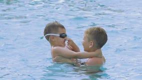 De jongen onderwijst de baby om zijn neus te sluiten en in de pool te duiken stock videobeelden