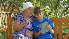 De jongen onderwijst haar grootmoeder hoe te om de tablet te gebruiken stock videobeelden