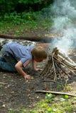 De jongen ontsteekt vuur Stock Afbeeldingen
