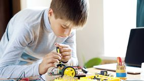 De jongen ontwerpt een elektronisch stuk speelgoed model Schroeft de ontbrekende schroef in de kring na de instructies stock videobeelden