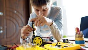 De jongen ontwerpt een elektronisch stuk speelgoed model Schroeft de ontbrekende schroef in de kring na de instructies stock footage