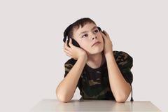 De jongen in oortelefoons Stock Afbeelding