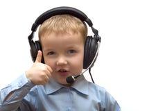 De jongen in oortelefoons toont gebaar Stock Foto's