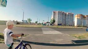 De jongen op een kinderen` s fiets kruist de straat op een voetgangersoversteekplaats stock footage