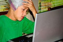 De jongen op laptop beklemtoonde met hoofdpijn Royalty-vrije Stock Afbeelding