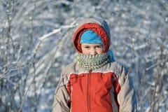 De jongen in openlucht in zonne en zeer koude dag Stock Afbeeldingen