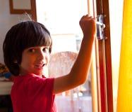 De jongen opent de deur van een nieuw huis Stock Fotografie