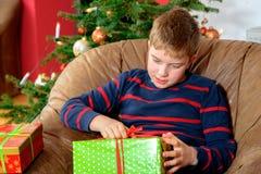 De jongen opent zijn Kerstmis voorstelt Royalty-vrije Stock Afbeeldingen
