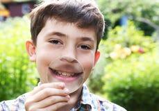 De jongen overdrijft zijn lippen met vergrootglas Stock Foto's