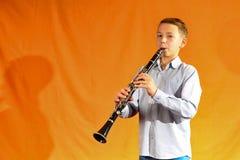 De jongen in overhemd en jeans speelt de klarinet op een gele achtergrond stock afbeeldingen
