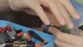 De jongen plaatst één element van de robot stock footage