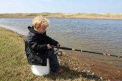 De jongen probeert om sommige vissen te vangen Stock Foto's