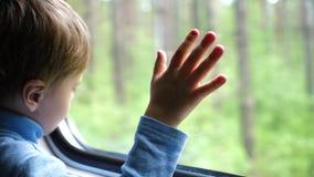 De jongen reist door trein en kijkt uit het venster, lettend op de bewegende voorwerpen buiten het venster Handclose-up stock footage