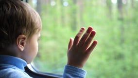De jongen reist door trein en kijkt uit het venster, lettend op de bewegende voorwerpen buiten het venster Handclose-up stock videobeelden