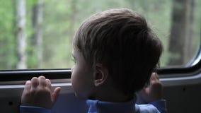 De jongen reist door trein en kijkt uit het venster, lettend op de bewegende voorwerpen buiten het venster Het reizen met stock video