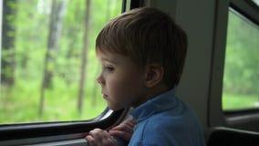 De jongen reist door trein en kijkt uit het venster, lettend op de bewegende voorwerpen buiten het venster Het reizen met stock videobeelden