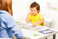 De jongen richt de kaarten van dagactiviteiten Stock Foto's