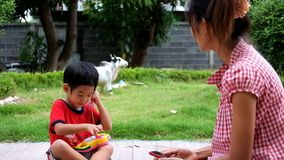 De jongen roept aan moeder met stuk speelgoed telefoon stock video