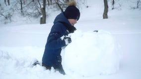 De jongen rolt grote sneeuwbal voor sneeuwman in de winter stock videobeelden