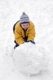 De jongen rolt sneeuw die royalty-vrije stock afbeeldingen