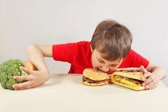 De jongen in rood bij de lijst kiest tussen fastfood en groente en vruchten op witte achtergrond stock fotografie
