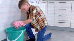 De jongen in rubberhandschoenen drukt de doek over de emmer en wast keukenvloer Het huisplichten van het kind stock video