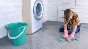 De jongen in rubberhandschoenen wast de vloer in de keuken Het huisplichten van het kind stock footage
